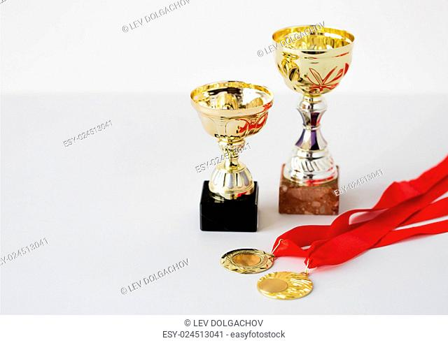 sport, achievement, reward, championship and success concept - close up of sports golden cups and medals on white background