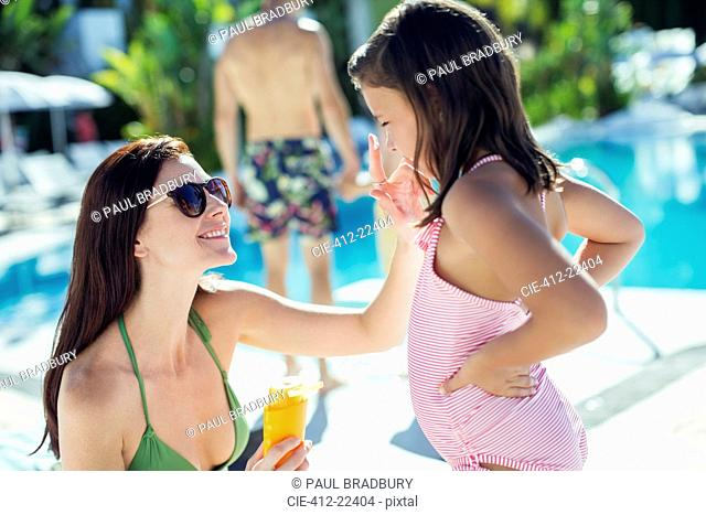 Mother applying suntan lotion on daughter's face by swimming pool