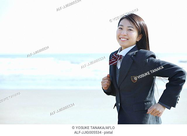 Young Japanese woman in a high school uniform running by the sea, Chiba, Japan
