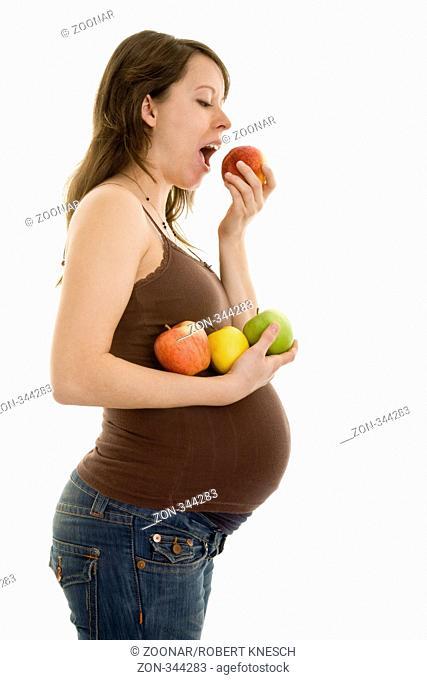 Schwangere Frau beiß in einen Pfirsisch und hält Äpfel in der Hand