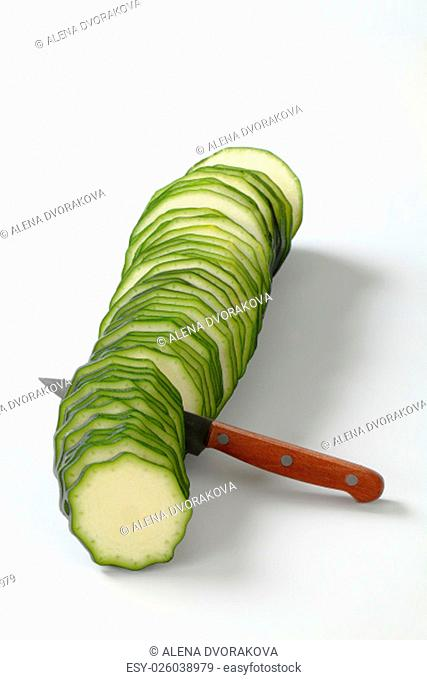 line of thin slices of fresh zucchini with a knife on a white background