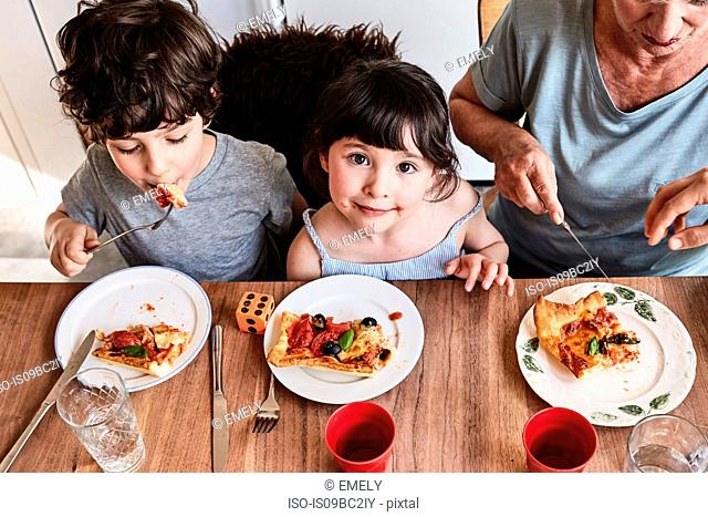 Grandmother sitting at kitchen table with grandchildren, eating pizza, elevated view