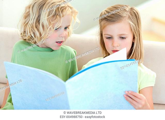 Siblings on the sofa reading magazine