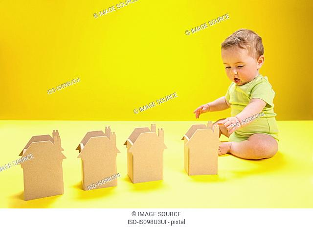 Baby boy playing with cardboard houses