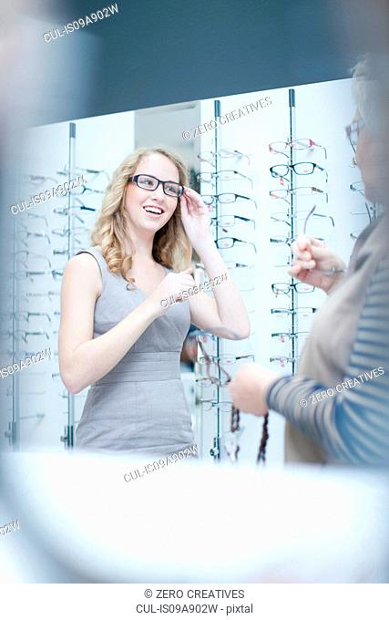 Young woman trying on eyeglasses in shop