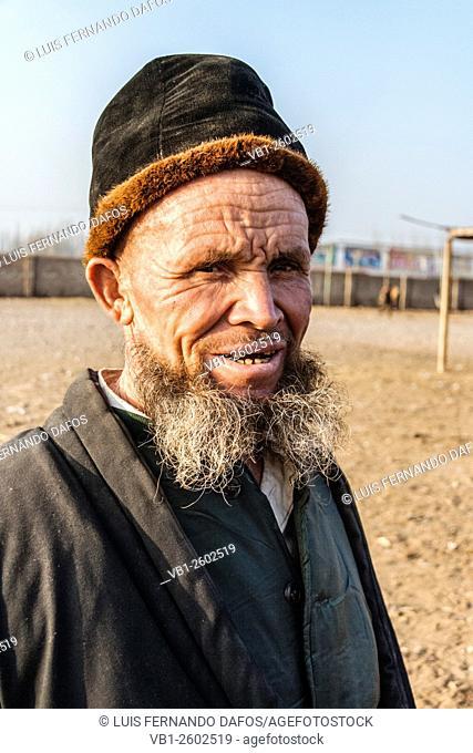 Old Uyghur man portrait with fur hat and beard at Mal Bazaar livestock weekly market. Kashgar, Xinjiang, China
