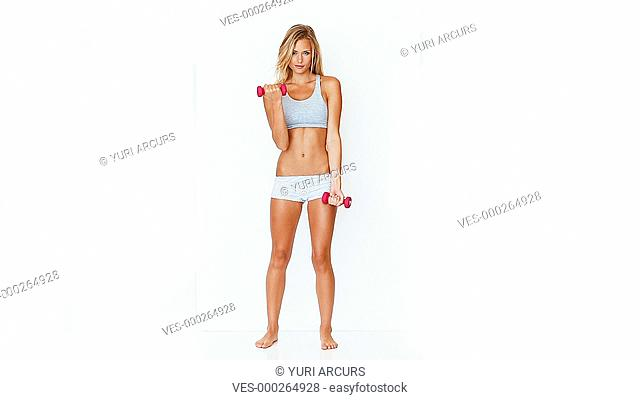 Cute fit woman doing bicep curls with some small dumbbells while isolated on white
