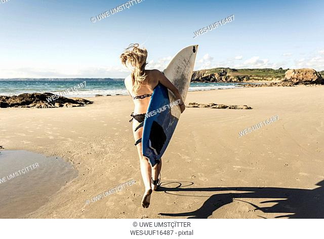 Young woman running on the beach, carrying surfboard