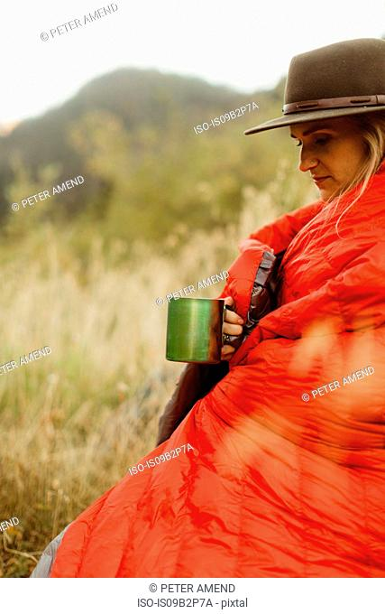 Woman sitting in rural setting, wrapped in sleeping bag, holding tin mug, Mineral King, Sequoia National Park, California, USA
