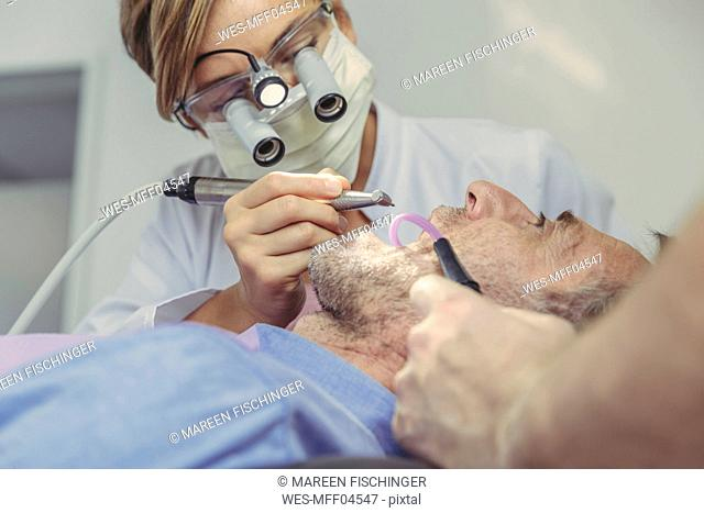 Patient getting dental treatment, dentist using dental drill and head magnifiers and light