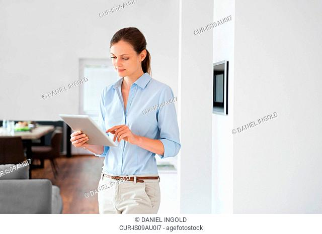 Woman using digital tablet to control home automation system