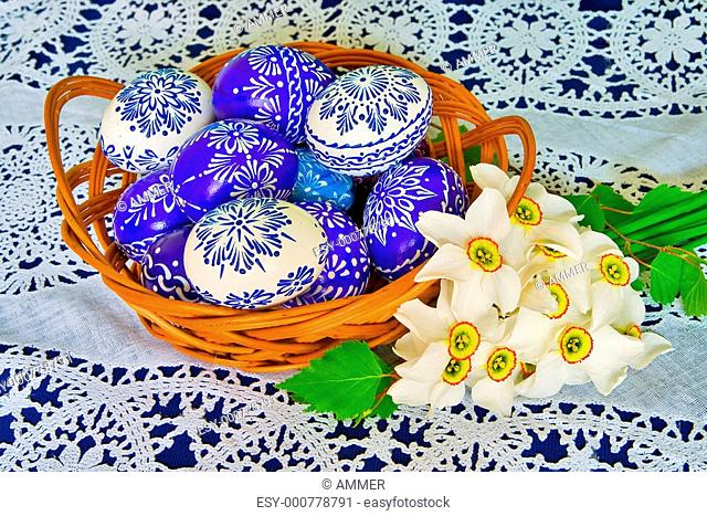 Blue ornamental Easter eggs and bouquet of daffodils