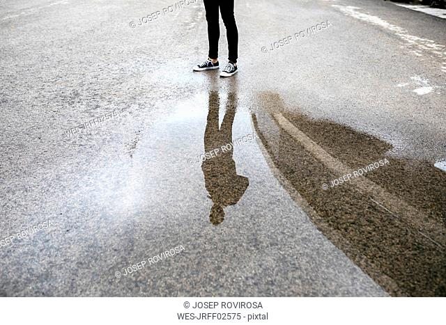 Reflection of a man in a puddle on the floor
