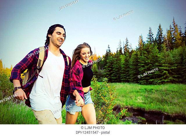 Young couple running while holding hands in a city park in autumn; Edmonton, Alberta, Canada