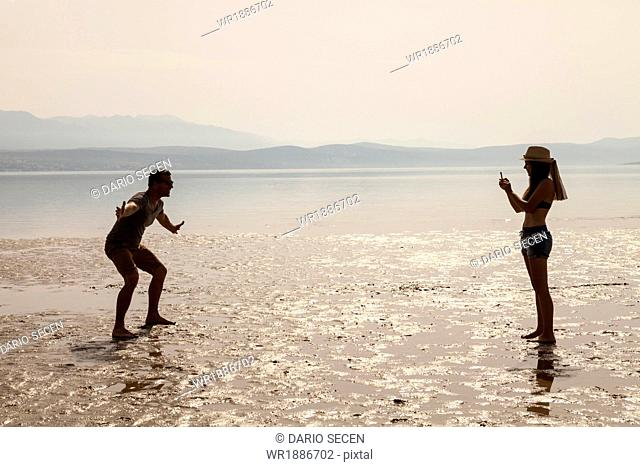 Croatia, Young woman on beach taking pictures