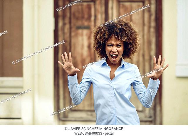 Portrait of woman with afro hairstyle screaming outdoors