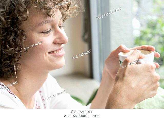 Smiling young woman sitting in a coffee shop with cup of coffee