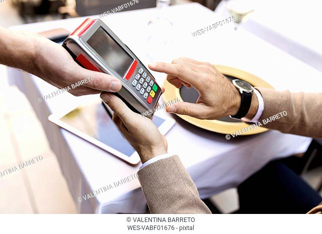 Man entering pin into card reader in a restaurant