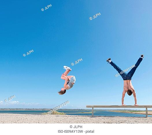 Girl doing somersault, boy doing handstand on beach bench