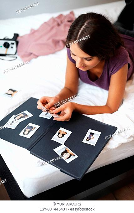 Girl lying down on bed while putting together a photo album