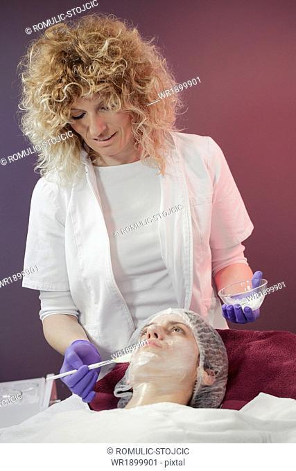 Woman receiving a facial mask