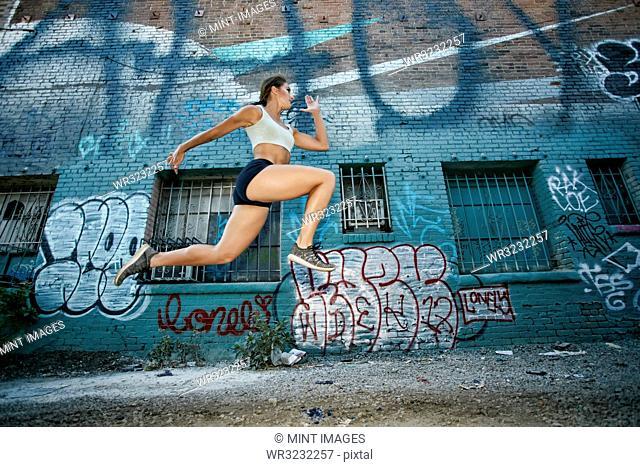Female athlete running along street past blue building covered in graffiti