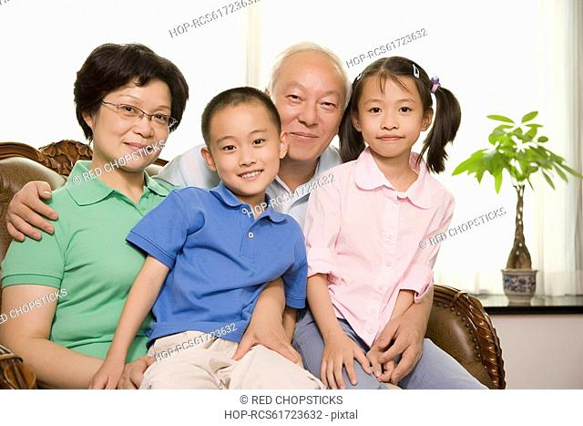 Portrait of a mature couple sitting with their grandchildren