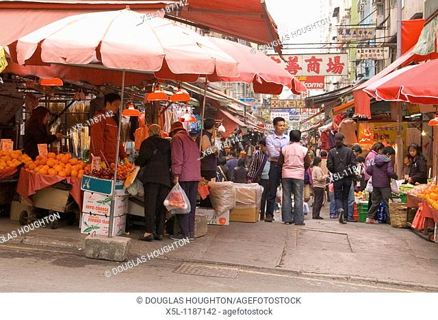 TAIPO HONG KONG Shopkeeper and customers fruit stall shop crowds in market alley