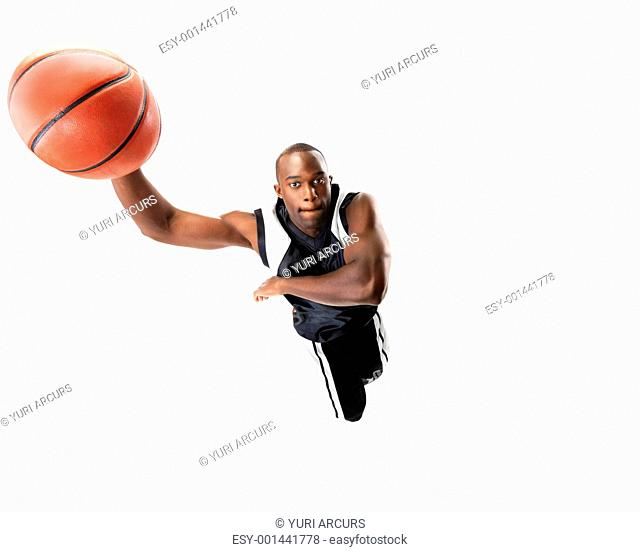 Portrait of a young male basketball player jumping in air trying to dunk the ball