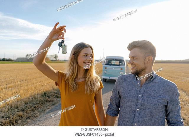 Young couple with car key on dirt track at camper van in rural landscape