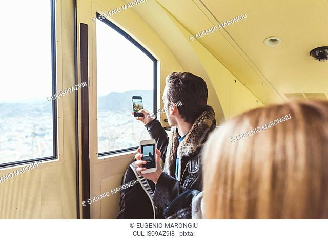 Young man taking smartphone photographs through funicular window, Como, Italy