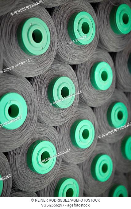production of fine woolen fabrics for suits - in a factory in Sabadell, Spain. rolls of woolen threads