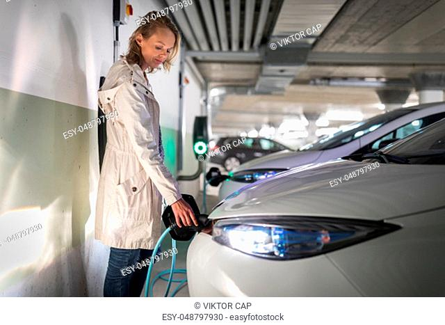 Young woman charging an electric vehicle in an underground garage equiped with e-car charger. Car sharing concept