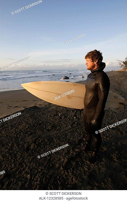 Surfer holding surfboard looking at ocean at sunset, Southeast Alaska; Yakutat, Alaska, United States of America