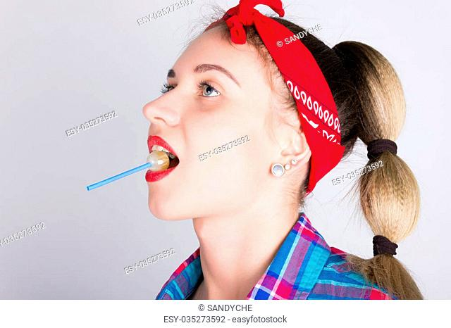 close-up beautiful young leggy blondy girl in a red bandana, denim overalls and a plaid shirt, licking candy