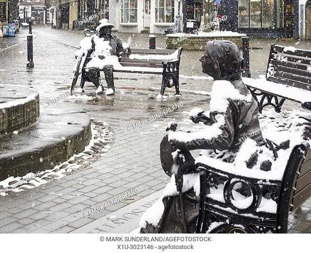 Snow falling on the Blind Jack and Mother Shipton statues in the Market Place at Knaresborough North Yorkshire England