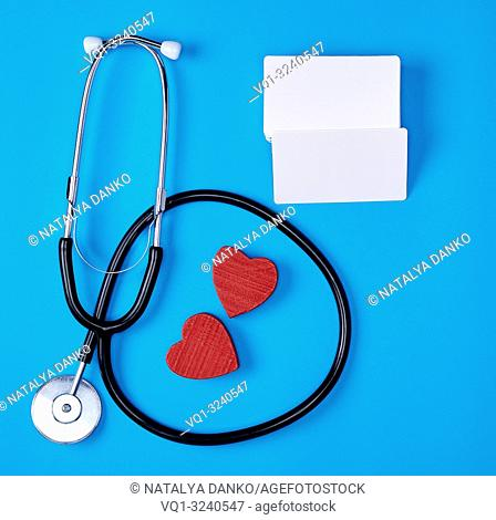 medical stethoscope and empty paper business cards on a blue background