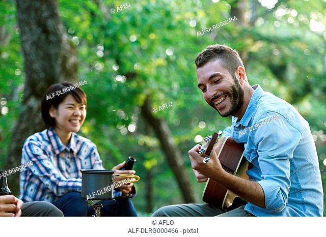 Friends playing guitar at a camp site