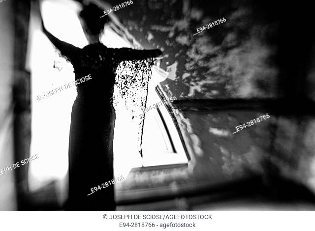 Silhouette back view of a woman in front of a window in an abandoned building, black & white