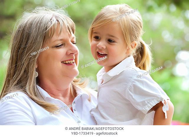 Grandmother holding her cute granddaughter of four years