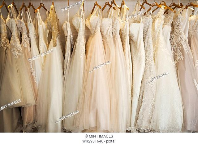 Rows of wedding dresses on display in a specialist wedding dress shop. A variety of colour tones and styles, fashionable lace and boned bodices