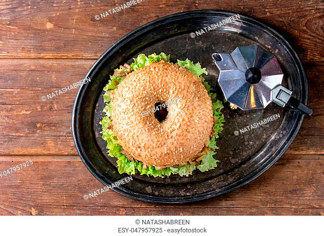Bagel with stew beef, fresh salad and fried onion served on vintage metal tray with coffee pot over wooden table. Top view