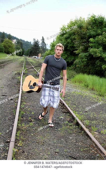 A young caucasian male with his guitar outdoors