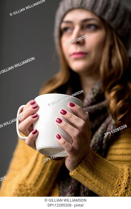 Nicaraguan woman holding a cup of tea; Toronto, Ontario, Canada