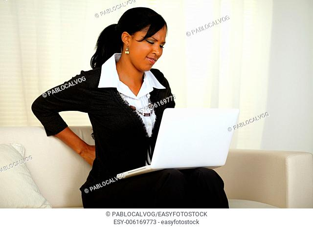 Portrait of a young businesswoman with back pain that is working on laptop at home indoor