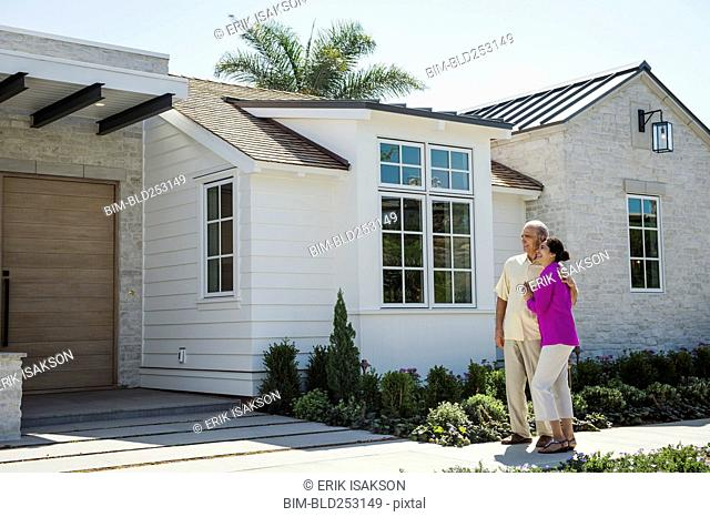 Older couple standing near driveway of house