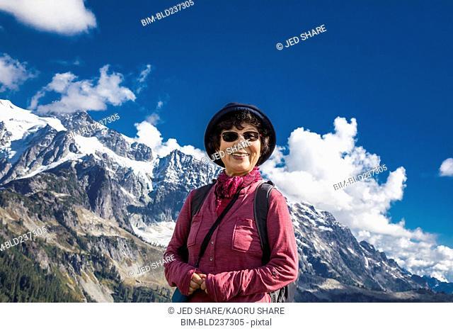 Older Japanese woman posing near mountain