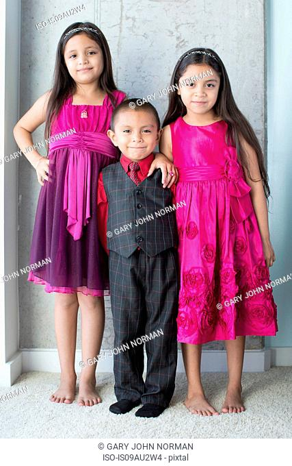 Portrait of three siblings, wearing party clothes