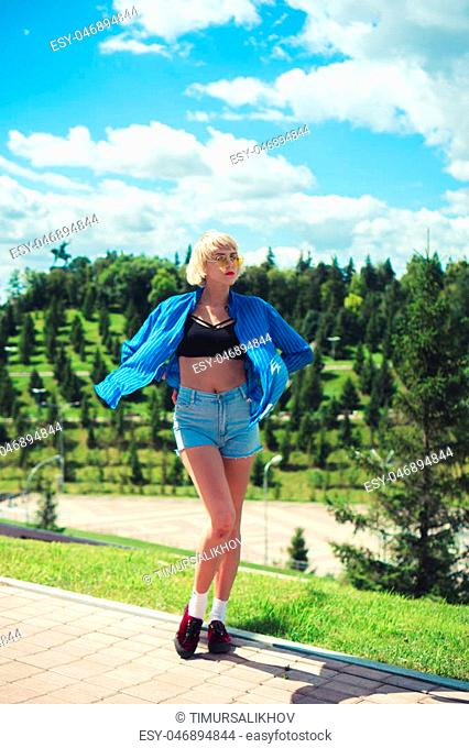 young white haired woman student enjoys in park sunny weather in Ufa
