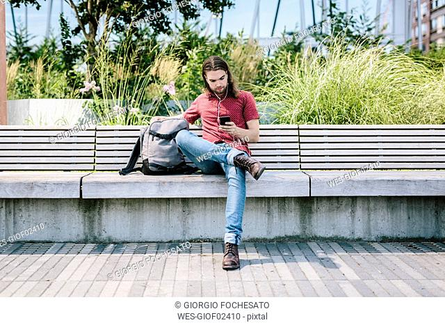 Man sitting on a bench with earbuds using cell phone